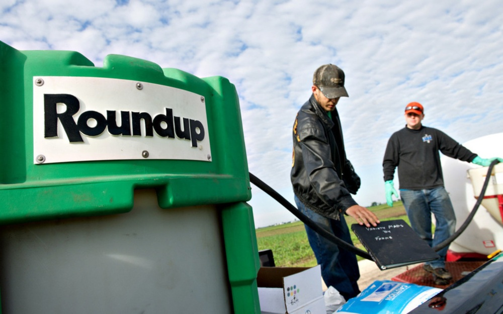Caption:Farmers Matt Wiggeim, right, and Cody Gibson mix Monsanto Co.'s Roundup herbicide near a corn field in Kasbeer, Illinois, U.S., on Monday, June 13, 2011. Corn fell to a one-month low and soybeans declined on speculation that favorable weather will boost yields in the U.S., the world's biggest grower and exporter. Photographer: Daniel Acker/Bloomberg via Getty Images